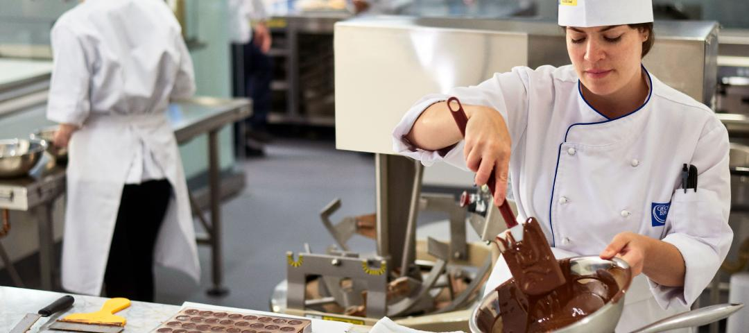 Baking arts students working with chocolate in a culinary lab.