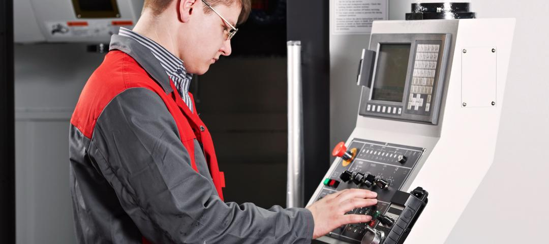 Operator checks the controls panel for an automated industrial manufacturing process.